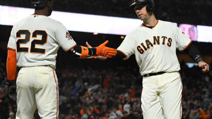 SAN FRANCISCO, CA - MAY 14: Andrew McCutchen #22 and Buster Posey #28 of the San Francisco Giants congratulate each other after they both scored on a two-run rbi double from Brandon Belt #9 against the Cincinnati Reds in the bottom of the six inning at AT&T Park on May 14, 2018 in San Francisco, California. (Photo by Thearon W. Henderson/Getty Images)