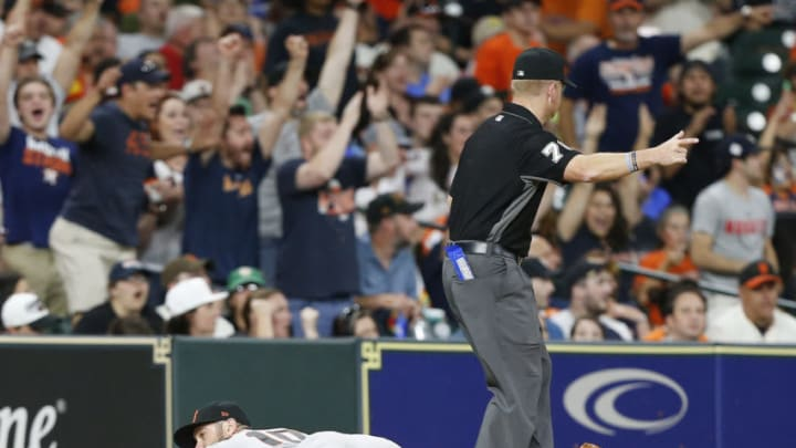 HOUSTON, TX - MAY 22: Third base umpire Mike Muchlinski signals a fair ball after Evan Longoria #10 of the San Francisco Giants dives for and misses 2a ball hit by Jose Altuve #27 of the Houston Astros in the sixth inning at Minute Maid Park on May 22, 2018 in Houston, Texas. (Photo by Bob Levey/Getty Images)