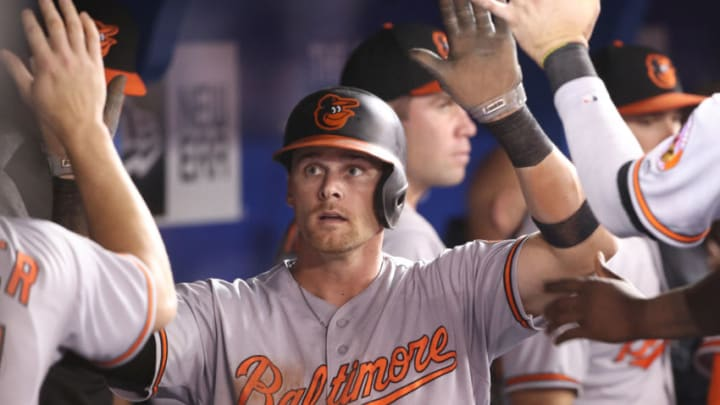 TORONTO, ON - AUGUST 20: Craig Gentry #14 of the Baltimore Orioles is congratulated by teammates in the dugout after scoring a run in the sixth inning during MLB game action against the Toronto Blue Jays at Rogers Centre on August 20, 2018 in Toronto, Canada. (Photo by Tom Szczerbowski/Getty Images)