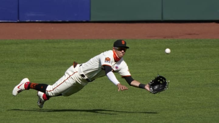 Mauricio Dubón #1 of the SF Giants makes a diving catch taking a hit away from Vimael Machin #39 of the Oakland Athletics in the top of the ninth inning at Oracle Park on August 16, 2020 in San Francisco, California. The Athletics won the game 15-3. (Photo by Thearon W. Henderson/Getty Images)