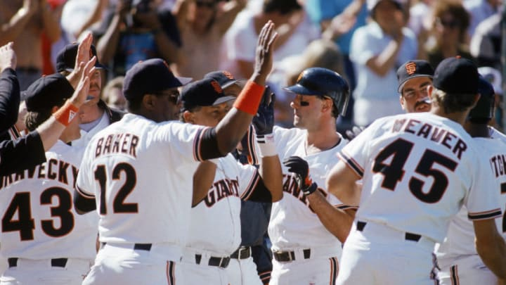 SAN FRANCISCO - OCTOBER: Manager Dusty Baker #12 and Will Clark #22 of the San Francisco Giants high five teammates against the Chicago Cubs during the 1989 National League Championship Series at Candlestick Park in October 1989 in San Francisco, California. (Photo by Otto Greule Jr/Getty Images)