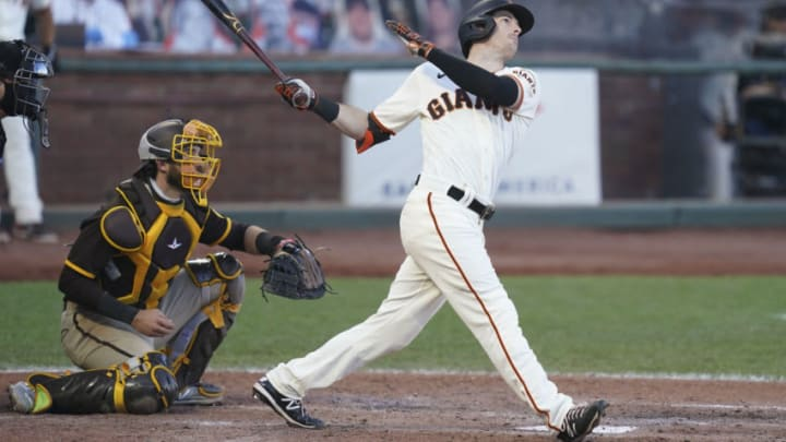 September 25, 2020; San Francisco, California, USA; San Francisco Giants right fielder Mike Yastrzemski (right) hits a two-run home run against San Diego Padres catcher Austin Nola (left) during the fourth inning of game one of a double header at Oracle Park. Mandatory Credit: Kyle Terada-USA TODAY Sports