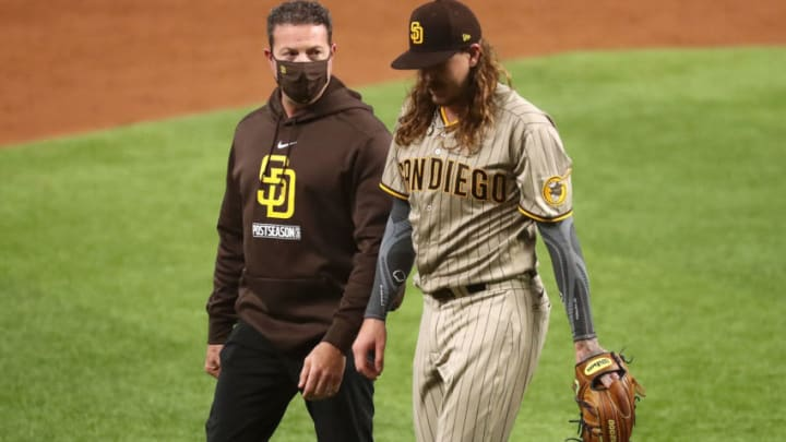 Oct 6, 2020; Arlington, Texas, USA; San Diego Padres starting pitcher Mike Clevinger (52) walks off the field with a trainer after he was removed from the game during the second inning in game one of the 2020 NLDS against the Los Angeles Dodgers at Globe Life Field. Mandatory Credit: Kevin Jairaj-USA TODAY Sports
