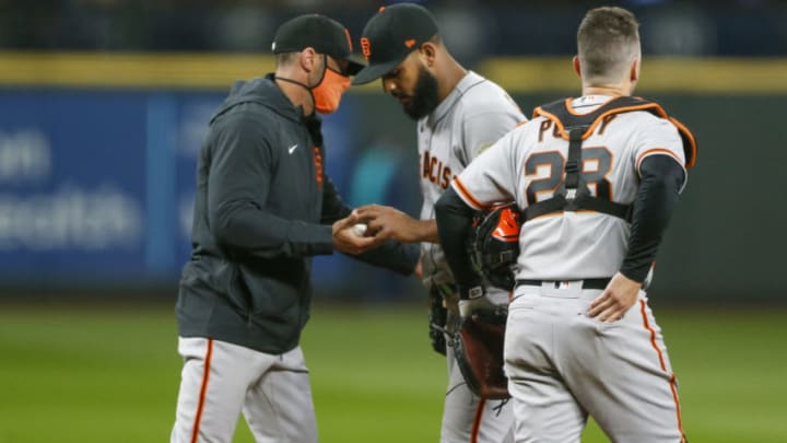 SF Giants manager Gabe Kapler (19, left) takes the ball from relief pitcher Jarlin Garc'a (66) during an eighth inning pitching change against the Seattle Mariners at T-Mobile Park. Mandatory Credit: Joe Nicholson-USA TODAY Sports