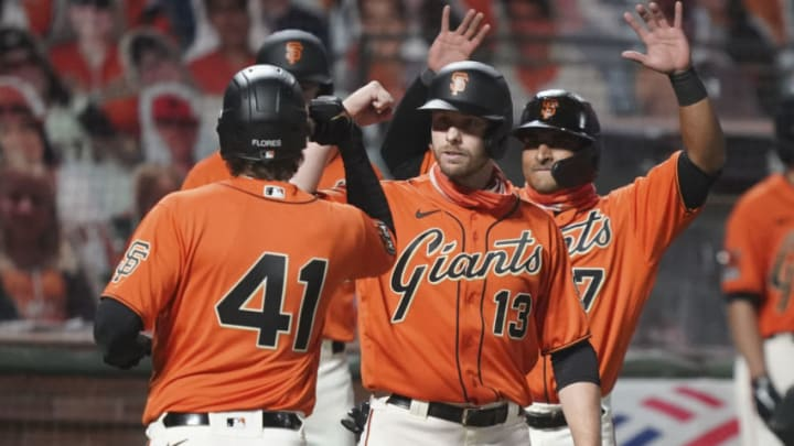 September 25, 2020; San Francisco, California, USA; San Francisco Giants designated hitter Wilmer Flores (41) is congratulated by right fielder Austin Slater (13) and second baseman Donovan Solano (7) after hitting a three-run home run against the San Diego Padres during the sixth inning of game two of a double header at Oracle Park. Mandatory Credit: Kyle Terada-USA TODAY Sports