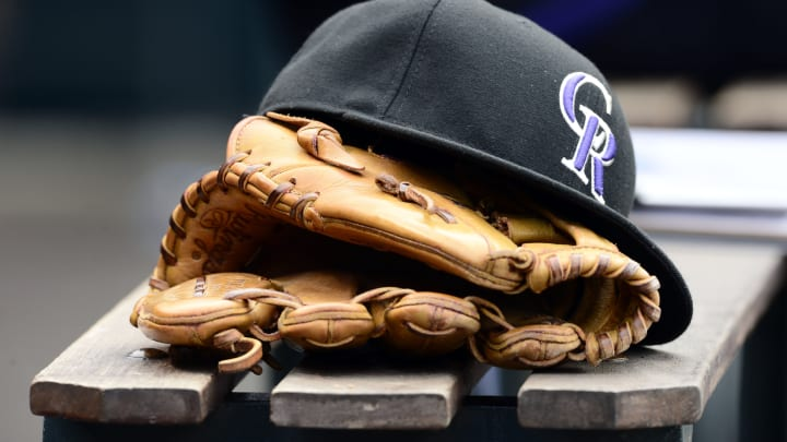May 10, 2015; Denver, CO, USA; General view of a Colorado Rockies glove and hat during the seventh inning of the game against the Los Angeles Dodgers at Coors Field. The Dodgers defeated the Rockies 9-5. Mandatory Credit: Ron Chenoy-USA TODAY Sports