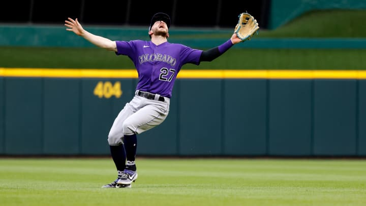 Trevor Story #27 of the Colorado Rockies fields a fly ball during the game against the Cincinnati Reds.