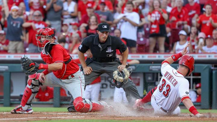 Jesse Winker #33 of the Cincinnati Reds slides into home plate to score a run.