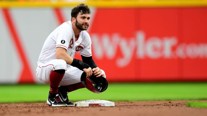 Tyler Naquin #12 of the Cincinnati Reds kneels by second base after a double in the first inning.
