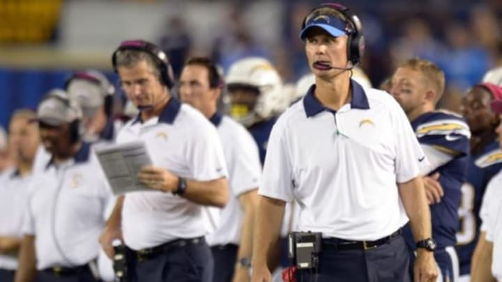 Oct 12, 2015; San Diego, CA, USA; San Diego Chargers head coach Mike McCoy (right) looks on as offensive coordinator Frack Reich (background, middle) looks at his play book during the fourth quarter against the Pittsburgh Steelers at Qualcomm Stadium. Mandatory Credit: Jake Roth-USA TODAY Sports