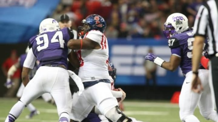 Dec 31, 2014; Atlanta , GA, USA; Mississippi Rebels offensive lineman Laremy Tunsil (78) has his leg caught as he clocks TCU Horned Frogs defensive end Josh Carraway (94) during the second quarter in the 2014 Peach Bowl at the Georgia Dome. Mandatory Credit: Jason Getz-USA TODAY Sports