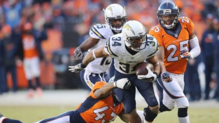 Jan 3, 2016; Denver, CO, USA; San Diego Chargers running back Donald Brown (34) runs the ball while Denver Broncos strong safety T.J. Ward (43) and cornerback Chris Harris (25) attempts to make the tackle during the second half at Sports Authority Field at Mile High. The Broncos won 27-20. Mandatory Credit: Chris Humphreys-USA TODAY Sports
