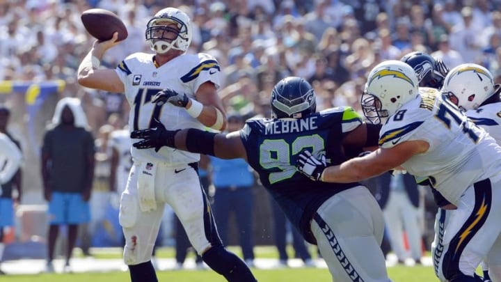 Sep 14, 2014; San Diego, CA, USA; San Diego Chargers quarterback Philip Rivers (17) throws a third quarter touchdown to tight end Antonio Gates (not pictured) while eluding the grasp of Seattle Seahawks defensive tackle Brandon Mebane (92) at Qualcomm Stadium. Mandatory Credit: Robert Hanashiro-USA TODAY Sports