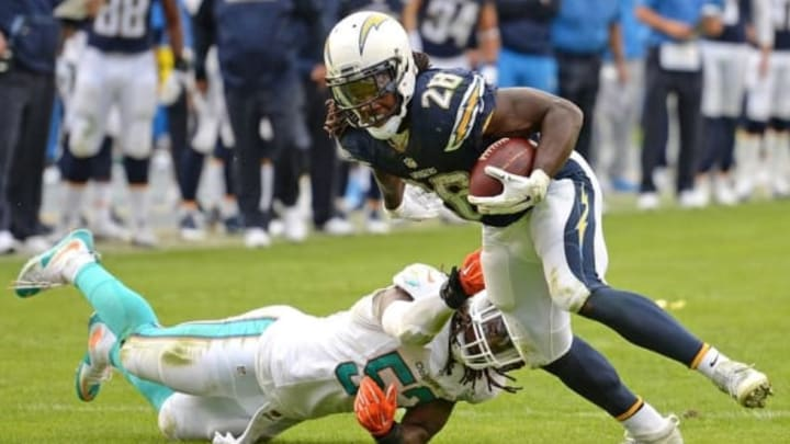 Dec 20, 2015; San Diego, CA, USA; San Diego Chargers running back Melvin Gordon (28) is defended by Miami Dolphins middle linebacker Kelvin Sheppard (52) on a second quarter run at Qualcomm Stadium. Mandatory Credit: Jake Roth-USA TODAY Sports