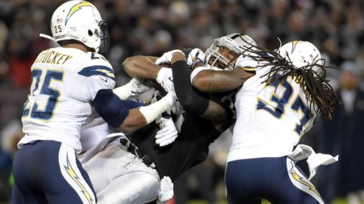 Dec 24, 2015; Oakland, CA, USA; Oakland Raiders tight end Clive Walford (88) is tackled by San Diego Chargers defensive back Darrell Stuckey (25) and strong safety Jahleel Addae (37) during an NFL football game at O.co Coliseum. Mandatory Credit: Kirby Lee-USA TODAY Sports