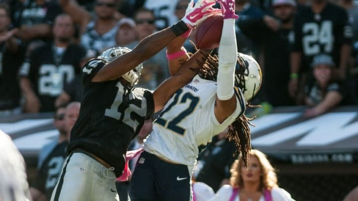 Oct 12, 2014; Oakland, CA, USA; San Diego Chargers cornerback Jason Verrett (22) intercepts the ball against Oakland Raiders wide receiver Brice Butler (12) during the fourth quarter at O.co Coliseum. The San Diego Chargers defeated the Oakland Raiders 31-28. Mandatory Credit: Ed Szczepanski-USA TODAY Sports