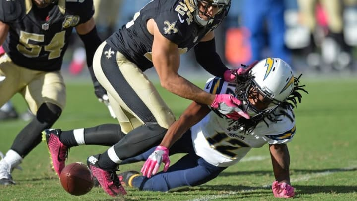 Oct 2, 2016; San Diego, CA, USA; San Diego Chargers wide receiver Travis Benjamin (12) fumbles the football as New Orleans Saints defensive back Sterling Moore (24) defends during the fourth quarter at Qualcomm Stadium. Mandatory Credit: Jake Roth-USA TODAY Sports
