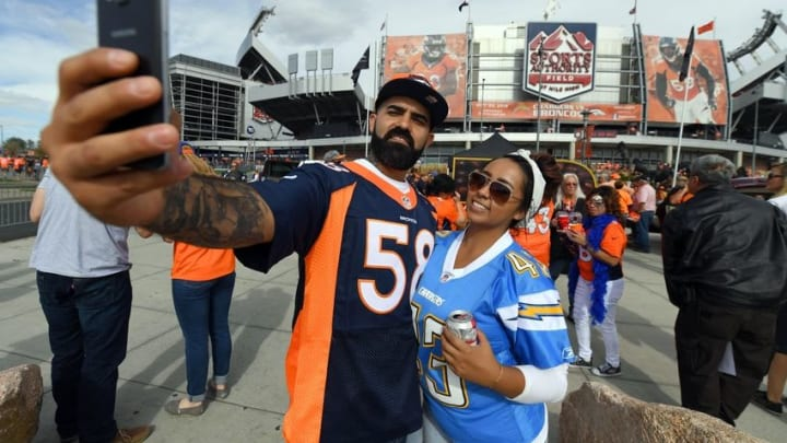 Oct 30, 2016; Denver, CO, USA; Denver Broncos and a San Diego Chargers fan take a photo outside of at Sports Authority Field at Mile High. Mandatory Credit: Ron Chenoy-USA TODAY Sports