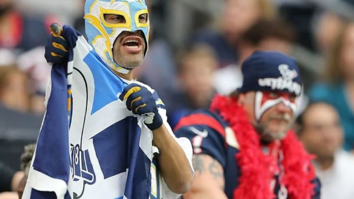 Nov 27, 2016; Houston, TX, USA; A San Diego Chargers fan cheers a Houston Texans looks on in the second half at NRG Stadium. San Diego Chargers won 21-13. Mandatory Credit: Thomas B. Shea-USA TODAY Sports