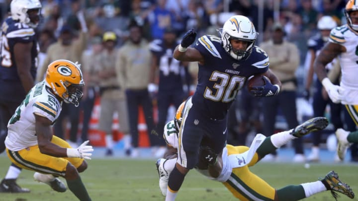 CARSON, CALIFORNIA - NOVEMBER 03: Austin Ekeler #30 of the Los Angeles Chargers splits the defense of Adrian Amos #31 and Will Redmond #25 of the Green Bay Packers during the second half of a game at Dignity Health Sports Park on November 03, 2019 in Carson, California. (Photo by Sean M. Haffey/Getty Images)