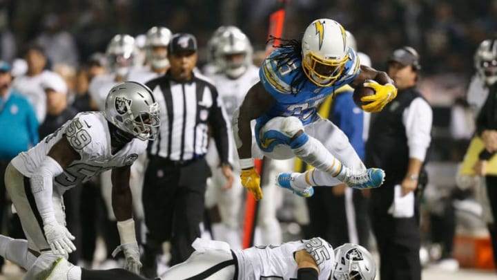 OAKLAND, CALIFORNIA - NOVEMBER 07: Melvin Gordon #25 of the Los Angeles Chargers jumps over Erik Harris #25 of the Oakland Raiders in the second quarter at RingCentral Coliseum on November 07, 2019 in Oakland, California. (Photo by Lachlan Cunningham/Getty Images)