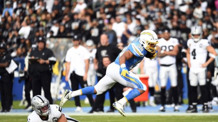 CARSON, CA - DECEMBER 22: Running back Austin Ekeler #30 of the Los Angeles Chargers breaks a tackle by inside linebacker Will Compton #51 of the Oakland Raiders during the first half at Dignity Health Sports Park on December 22, 2019 in Carson, California. (Photo by Kevork Djansezian/Getty Images)