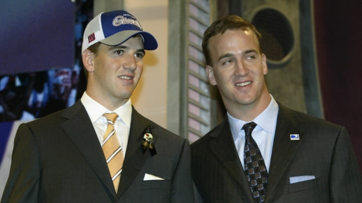 NEW YORK CITY – APRIL 24: Quarterback Eli Manning (Mississippi) stands next to his older brother QB Peyton Manning of the Indianapolis Colts after Eli was selected first overall by the San Diego Chargers at the 2004 NFL Draft on April 24, 2004, at Madison Square Garden in New York City. Manning was later traded to the New York Giants in exchange for QB Philip Rivers (North Carolina State) and New York's third-round pick (No. 65), which they use to select Iowa K Nate Kaeding, and the Giants' first-round and fifth-round picks in the 2005 draft. (Photo by Chris Trotman/Getty Images)