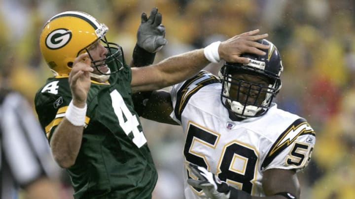 GREEN BAY, WI - AUGUST 11: Quarterback Brett Favre #4 of the Green Bay Packers is hit by linebacker Randall Godfrey #58 of the San Diego Chargers after throwing a pass during a preseason game at Lambeau Field on August 11, 2005 in Green Bay, Wisconsin. (Photo by Jonathan Daniel/Getty Images)