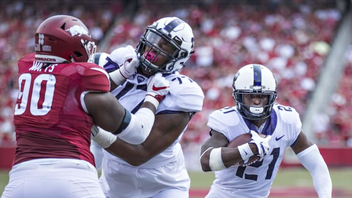 FAYETTEVILLE, AR – SEPTEMBER 9: Kyle Hicks #21 runs the ball behind the blocking of Lucas Niang #77 of the TCU Horned Frogs during a game against the Arkansas Razorbacks at Donald W. Reynolds Razorback Stadium on September 9, 2017, in Fayetteville, Arkansas. The Horn Frogs defeated the Razorbacks 28-7. (Photo by Wesley Hitt/Getty Images)