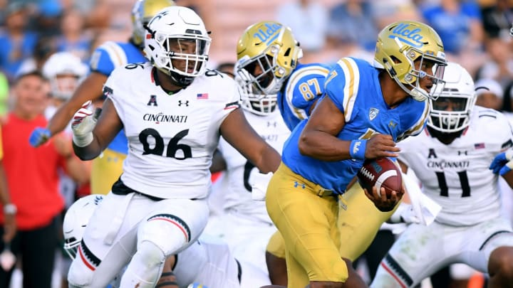 PASADENA, CA – SEPTEMBER 01: Dorian Thompson-Robinson #7 of the UCLA Bruins scrambles from Cortez Broughton #96 of the Cincinnati Bearcats during a 26-17 loss at Rose Bowl on September 1, 2018 in Pasadena, California. (Photo by Harry How/Getty Images)