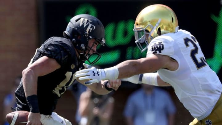 WINSTON SALEM, NC - SEPTEMBER 22: Drue Tranquill #23 of the Notre Dame Fighting Irish hits Sam Hartman #10 of the Wake Forest Demon Deacons during their game at BB&T Field on September 22, 2018 in Winston Salem, North Carolina. (Photo by Streeter Lecka/Getty Images)