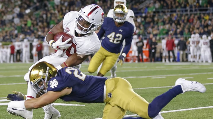 SOUTH BEND, IN – SEPTEMBER 29: Bryce Love #20 of the Stanford Cardina runs the ball and is tackled by Drue Tranquill #23 of the Notre Dame Fighting Irish during the first half of the game at Notre Dame Stadium on September 29, 2018 in South Bend, Indiana. (Photo by Michael Hickey/Getty Images)