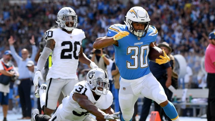 CARSON, CA – OCTOBER 07: Austin Ekeler #30 of the Los Angeles Chargers beats Marcus Gilchrist #31 and Obi Melifonwu #20 of the Oakland Raiders to score a touchdown to take a 10-3 lead during the second quarter at StubHub Center on October 7, 2018 in Carson, California. (Photo by Harry How/Getty Images)