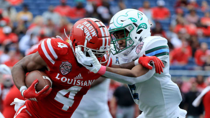 ORLANDO, FLORIDA - DECEMBER 15: Roderic Teamer Jr. #2 of the Tulane Green Wave tackles Raymond Calais #4 of the Louisiana-Lafayette Ragin Cajuns during the AutoNation Cure Bowl at Camping World Stadium on December 15, 2018 in Orlando, Florida. (Photo by Sam Greenwood/Getty Images)