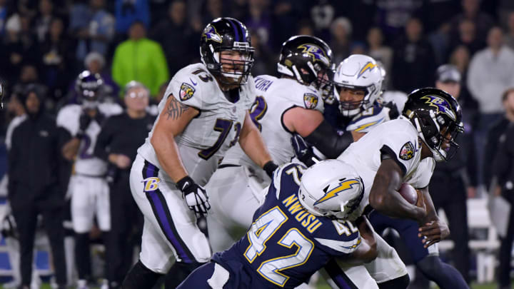 CARSON, CALIFORNIA – DECEMBER 22: Lamar Jackson #8 of the Baltimore Ravens is hit by Uchenna Nwosu #42 of the Los Angeles Chargers short of a first down during the first quarter at StubHub Center on December 22, 2018 in Carson, California. (Photo by Harry How/Getty Images)