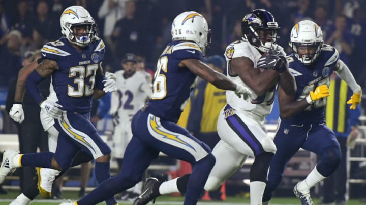 CARSON, CALIFORNIA - DECEMBER 22: Gus Edwards #35 of the Baltimore Ravens runs as he is chased by Michael Davis #43 and Casey Hayward #26 of the Los Angeles Chargers during the first quarter at StubHub Center on December 22, 2018 in Carson, California. (Photo by Harry How/Getty Images)