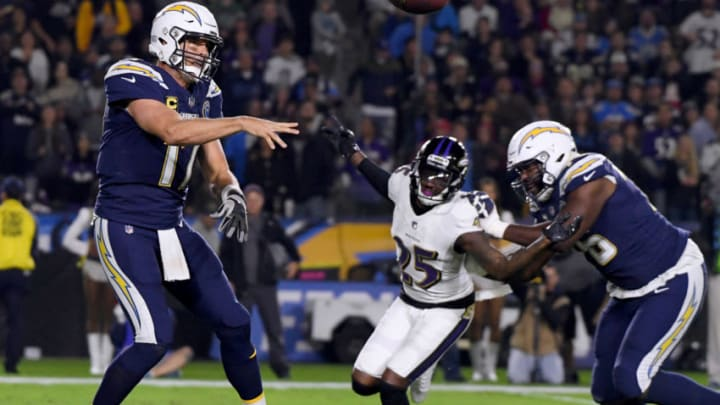 CARSON, CALIFORNIA - DECEMBER 22: Philip Rivers #17 of the Los Angeles Chargers makes a pass on the run in front of Tavon Young #25 of the Baltimore Ravens and Russell Okung #76 during the second quarter in a 22-10 Ravens win at StubHub Center on December 22, 2018 in Carson, California. (Photo by Harry How/Getty Images)