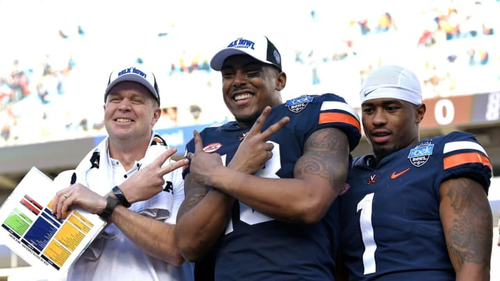 CHARLOTTE, NORTH CAROLINA – DECEMBER 29: Head coach Bronco Mendenhall, Chris Peace #13 and Jordan Ellis #1 of the Virginia Cavaliers celebrate after a win against the South Carolina Gamecocks during the Belk Bowl at Bank of America Stadium on December 29, 2018, in Charlotte, North Carolina. Virginia won 28-0. (Photo by Grant Halverson/Getty Images)
