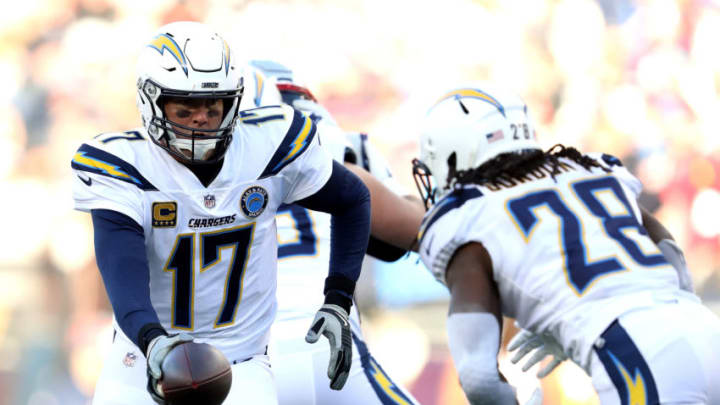 FOXBOROUGH, MASSACHUSETTS - JANUARY 13: Philip Rivers #17 of the Los Angeles Chargers hands the ball off to Melvin Gordon #28 during the second quarter in the AFC Divisional Playoff Game against the New England Patriots at Gillette Stadium on January 13, 2019 in Foxborough, Massachusetts. (Photo by Elsa/Getty Images)