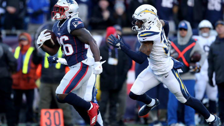 FOXBOROUGH, MASSACHUSETTS – JANUARY 13: Sony Michel #26 of the New England Patriots carries the ball as he is defended by Derwin James #33 of the Los Angeles Chargers during the second quarter in the AFC Divisional Playoff Game at Gillette Stadium on January 13, 2019 in Foxborough, Massachusetts. (Photo by Adam Glanzman/Getty Images)