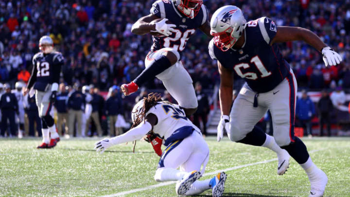 FOXBOROUGH, MASSACHUSETTS - JANUARY 13: Sony Michel #26 of the New England Patriots leaps over Jahleel Addae #37 of the Los Angeles Chargers during the first quarter in the AFC Divisional Playoff Game at Gillette Stadium on January 13, 2019 in Foxborough, Massachusetts. (Photo by Maddie Meyer/Getty Images)