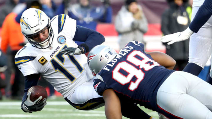 FOXBOROUGH, MASSACHUSETTS - JANUARY 13: Philip Rivers #17 of the Los Angeles Chargers is tackled by Trey Flowers #98 of the New England Patriots during the third quarter in the AFC Divisional Playoff Game at Gillette Stadium on January 13, 2019 in Foxborough, Massachusetts. (Photo by Al Bello/Getty Images)