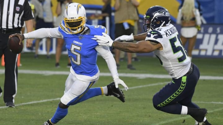 CARSON, CA - AUGUST 24: Tyrod Taylor #5 of the Los Angeles Chargers runs out of the pocket to get away from Mychal Kendricks #56 of the Seattle Seahawks in the first quarter during a pre-season NFL football game at Dignity Health Sports Park on August 24, 2019 in Carson, California. (Photo by John McCoy/Getty Images)