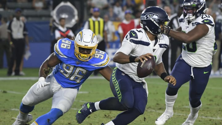 CARSON, CA – AUGUST 24: Russell Wilson #3 of the Seattle Seahawks avoids a tackle by Patrick Afriyie #96 of the Los Angeles Chargers in the first quarter during a pre-season NFL football game at Dignity Health Sports Park on August 24, 2019 in Carson, California. (Photo by John McCoy/Getty Images)