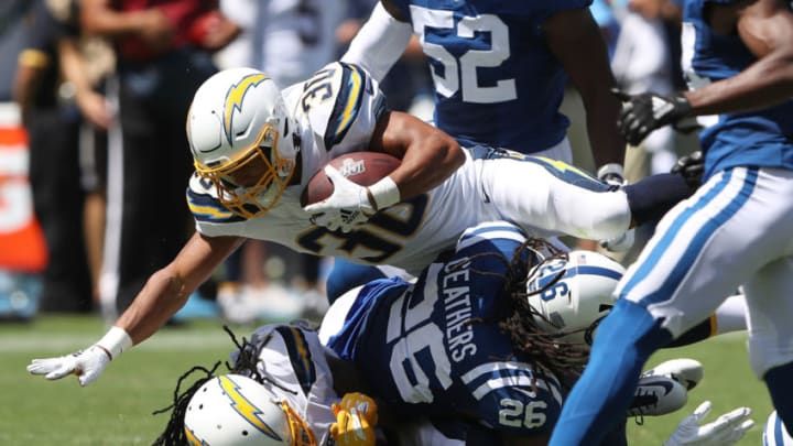 CARSON, CALIFORNIA - SEPTEMBER 08: Austin Ekeler #30 of the Los Angeles Chargers runs over Clayton Geathers #26 of the Indianapolis Colts on a short run during the first half of a game at Dignity Health Sports Park on September 08, 2019 in Carson, California. (Photo by Sean M. Haffey/Getty Images)