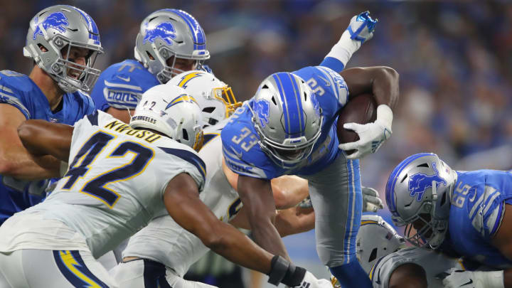 DETROIT, MICHIGAN – SEPTEMBER 15: Kerryon Johnson #33 of the Detroit Lions gets tripped up during a second-quarter run behind Uchenna Nwosu #42 of the Los Angeles Chargers at Ford Field on September 15, 2019, in Detroit, Michigan. (Photo by Gregory Shamus/Getty Images)