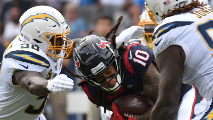 CARSON, CALIFORNIA - SEPTEMBER 22: Wide receiver DeAndre Hopkins #10 of the Houston Texans runs the ball through outside linebacker Thomas Davis #58 and defensive tackle Justin Jones #93 of the Los Angeles Chargers at Dignity Health Sports Park on September 22, 2019 in Carson, California. (Photo by Meg Oliphant/Getty Images)