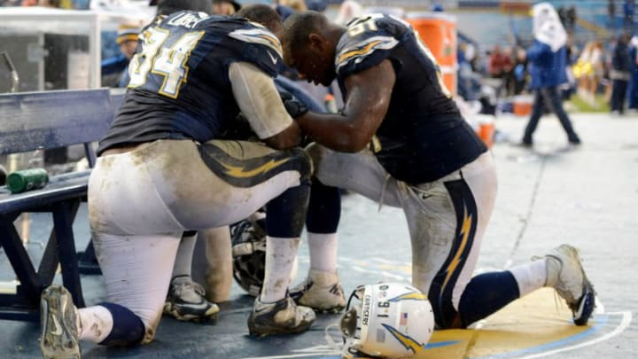 SAN DIEGO, CA - DECEMBER 30: Corey Liuget #94 and Kendall Reyes #91of the San Diego Chargers pray on the sidelines after the 24-21 win over the Oakland Raiders on December 30, 2012 at Qualcomm Stadium in San Diego, California. (Photo by Donald Miralle/Getty Images)