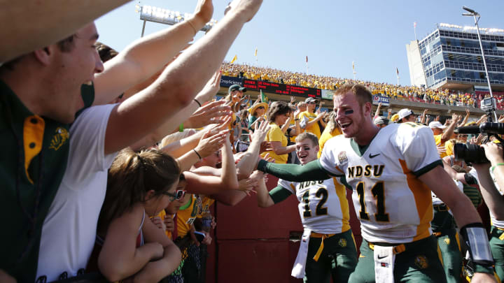 AMES, IA – AUGUST 30: Quarterbacks Carson Wentz #11 and quarterback Easton Stick #12 of the North Dakota State Bison celebrate with fans after defeating the Iowa State Cyclones 34-14 at Jack Trice Stadium on August 30, 2014 in Ames, Iowa. North Dakota State defeated Iowa State 34-14. (Photo by David Purdy/Getty Images)