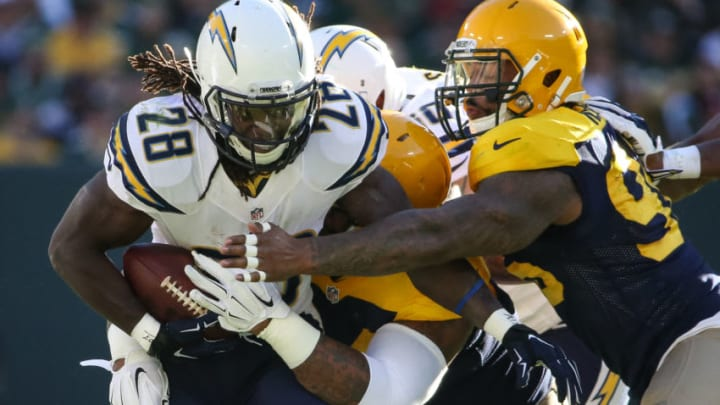 GREEN BAY, WI - OCTOBER 18: Melvin Gordon #28 of the San Diego Chargers gets the ball punched away as Mike Neal #96 of the Green Bay Packers reaches across in the first quarter at Lambeau Field on October 18, 2015 in Green Bay, Wisconsin. (Photo by Jonathan Daniel/Getty Images)